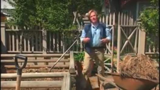 Image shows the author standing beside his compost bins.